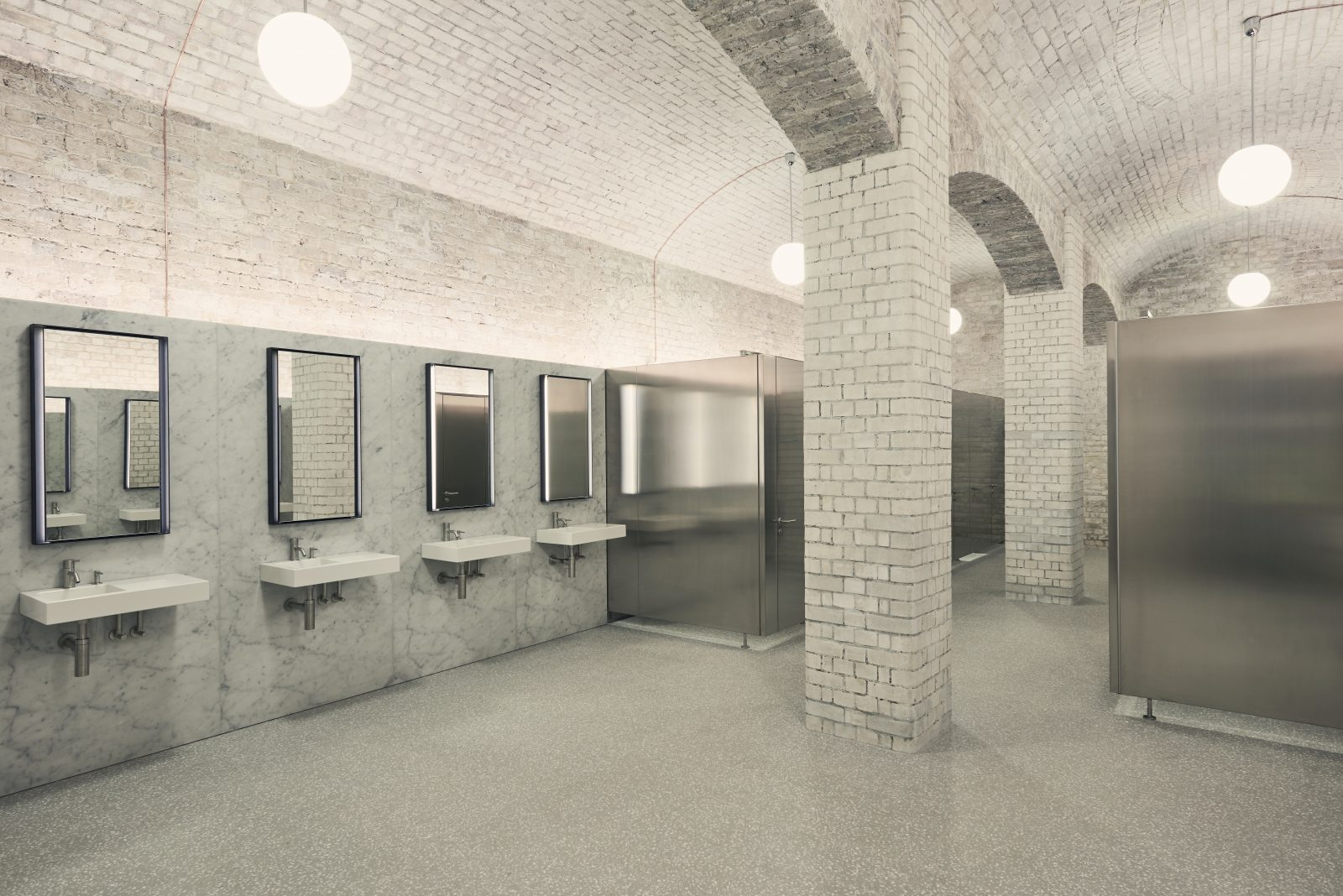 The toilet finishes comprise carrara marble walls and terazzo flooring